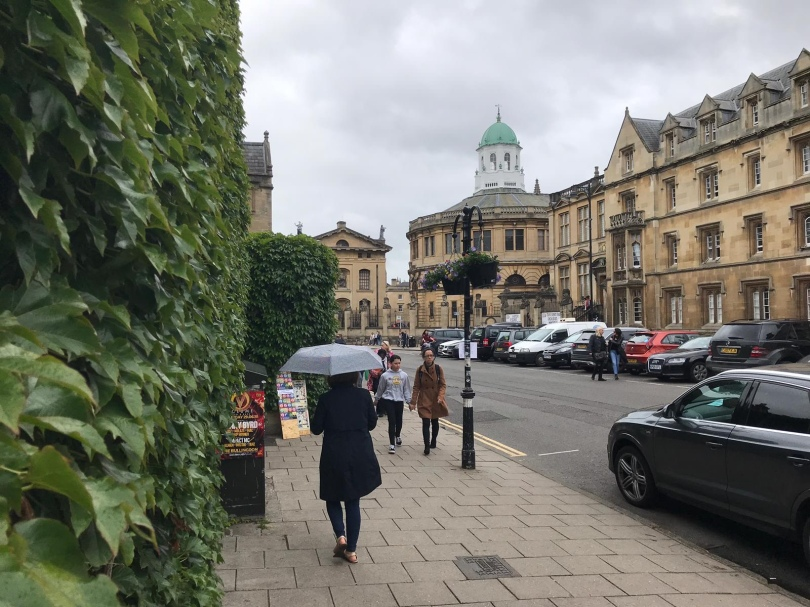 Girl walks through streets near Oxford University carrying an umbrella