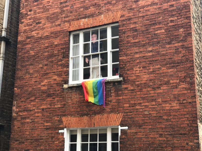 A cardboard cutout of actor Danny DeVito propped in a window above a Pride flag at Oxford University